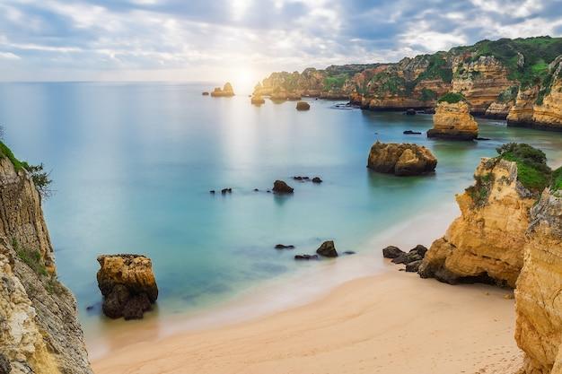 Morze plaża o zachodzie słońca. pochmurne niebo. portugalia, algarve, lagos.
