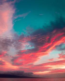 Morze pod zachmurzonym niebem podczas zapierającego dech w piersiach kolorowego zachodu słońca