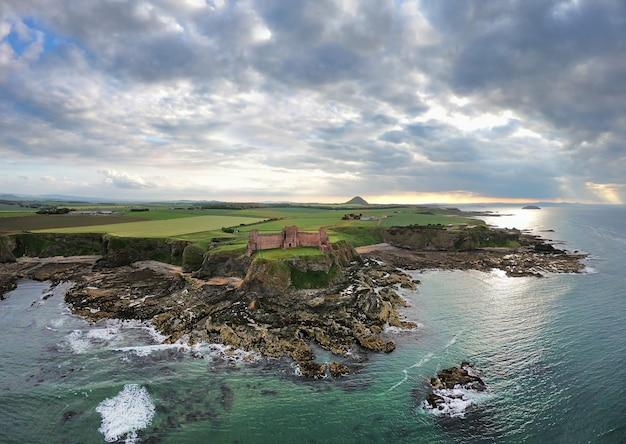 Morze północne o zachodzie słońca i widok na zamek tantallon z góry. north berwick. szkocja, wielka brytania