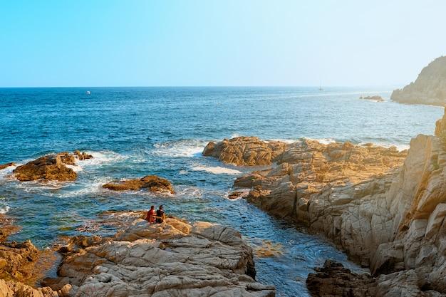 Morze. potomstwa dobierają się na skalistym wybrzeżu przy sunse