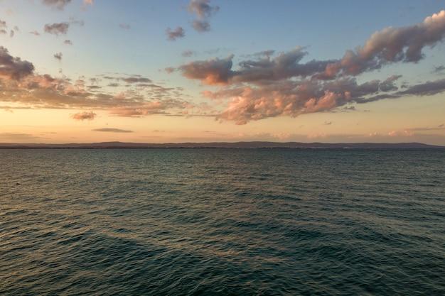 Morze powierzchnia z błękitnymi wodnymi fala pod żółtym i purpurowym zmierzchu niebem.