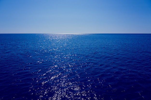 Morze wychodzi poza horyzont z błękitnym niebem w tle.
