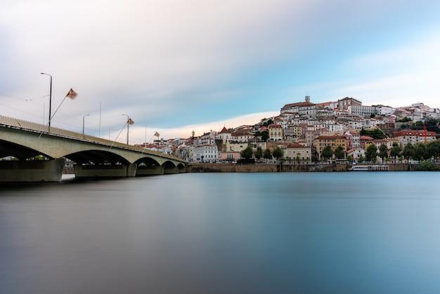 Morze z mostem na nim otoczonym miastem coimbra pod zachmurzonym niebem w portugalii