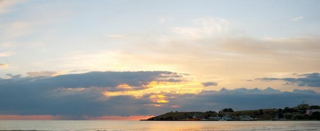 Morze zachód słońca z przylądka i statków. obraz złożony z dwóch ujęć.