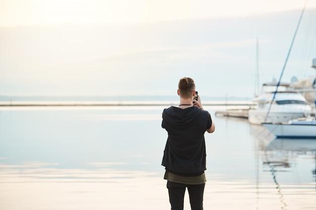 Morze zapiera dech w piersiach. widok z tyłu strzał stylowego młodego europejczyka w modnych ubraniach stojącego nad brzegiem morza, fotografującego morze i piękny jacht na smartfonie, będącego fotoreporterem lub amatorem