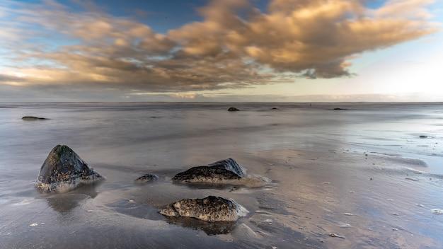 Morze ze skałami pod niebieskim pochmurnym niebem