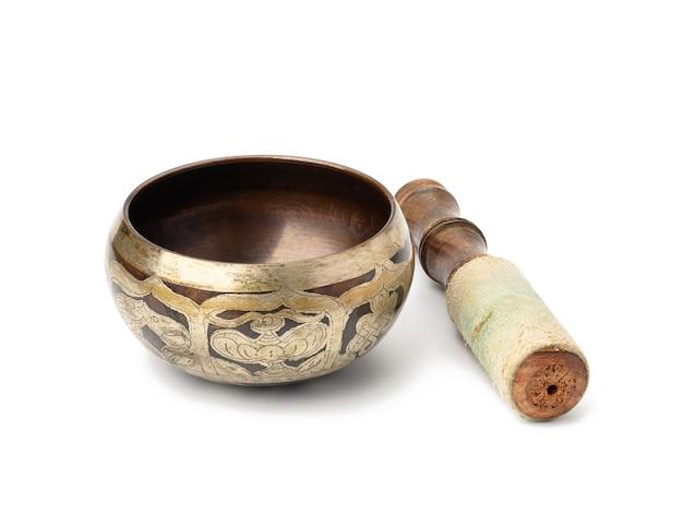 Mosiężna misa śpiewająca i drewniany młotek na białym tle na białej powierzchni. instrument muzyczny do medytacji, relaksu, różnych praktyk medycznych związanych z biorytmami, w jodze