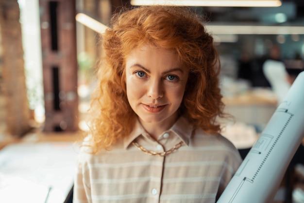 Mosiężne kręcone włosy. atrakcyjna niebieskooka kobieta z mosiężnymi kręconymi włosami nosząca stylowy naszyjnik