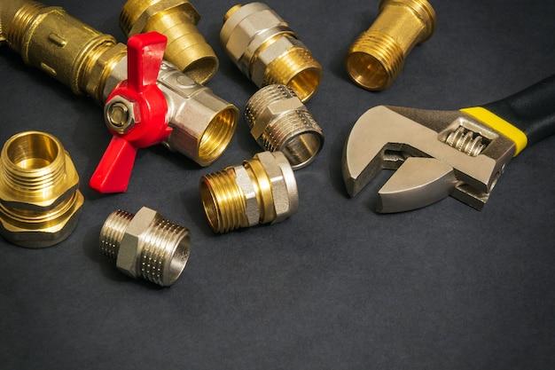 Mosiężne złączki hydrauliczne i klucz nastawny zamykają się na czarnym tle podczas naprawy lub wymiany części zamiennych