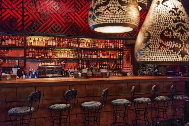 Moskwa, rosja, 01.01.2019, kontuar barowy, szafki z alkoholem, dużo krzeseł z rzędu, konstrukcja baru