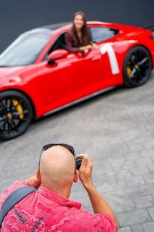 Moskwa. rosja. 13 sierpnia 2021 fotograf i czerwony samochód. profesjonalna sesja zdjęciowa czerwonego samochodu. fotograf trzyma aparat w dłoni.