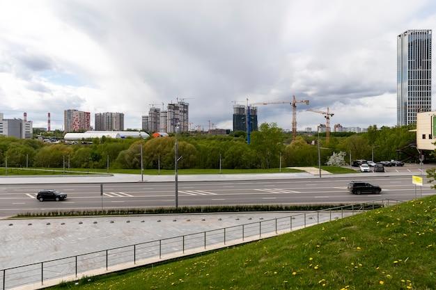 Moskwa / rosja - maj 2020: kilka dużych placów budowy z dużą liczbą dźwigów budowlanych pracujących przy budowie kompleksów mieszkaniowych na zachmurzonym niebie