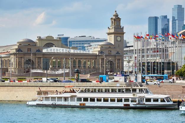 Moskwa rosja, maj, - 29, 2019: nowożytny riverboat na rzece w mieście, blisko centrów handlowych i dworca kolejowego. statek jest zacumowany w malowniczej nowoczesnej architekturze miejskiej.