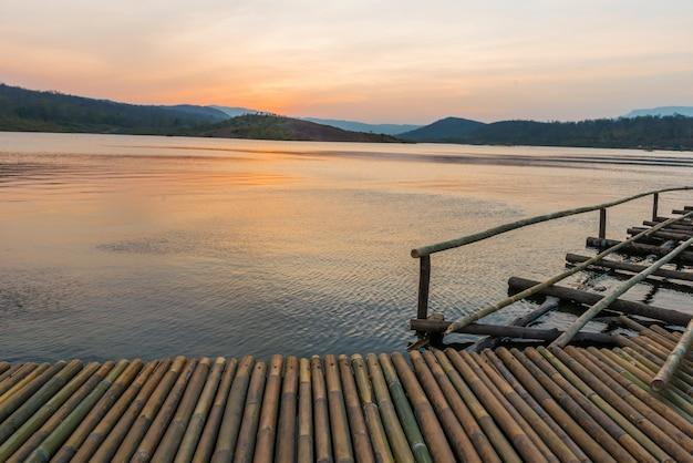 Most bambusowy w pobliżu jeziora w czasie wschodu słońca.