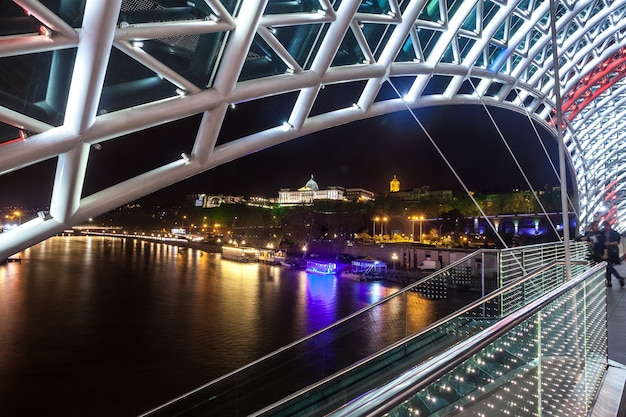Most dla pieszych pokoju nad rzeką mtkvari w tbilisi w nocy. flaga gruzińska.