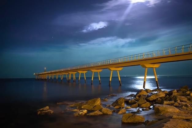 Most i morze z kamieniami nocą