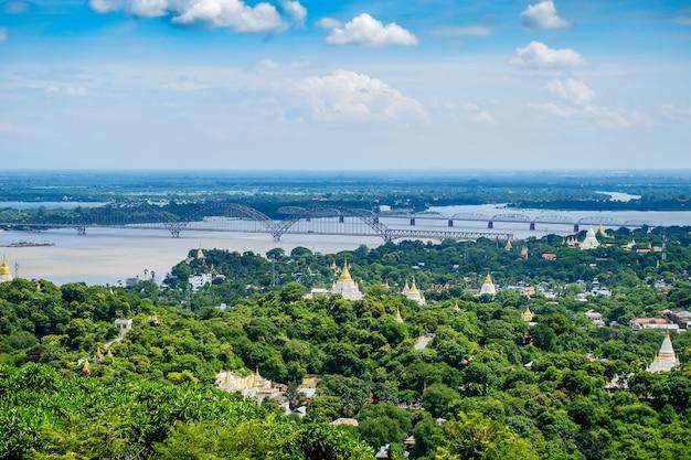 Most irrawaddy lub ayeyarwady, mosty yadanabon z miastem mandalay, świątyniami, pagodą, rzeką irrawaddy. widok ze wzgórza sagaing. punkt orientacyjny i popularny wśród turystów atrakcji w birmie