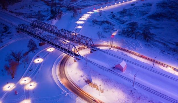 Most kolejowy nad rzeką na tle rozgwieżdżonego nieba. nocny letni wspaniały krajobraz.