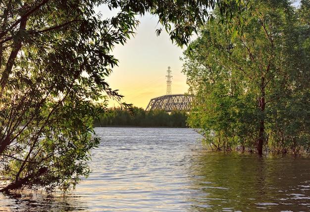 Most kolejowy w oddali przez rzekę ob podpora linii wysokiego napięcia