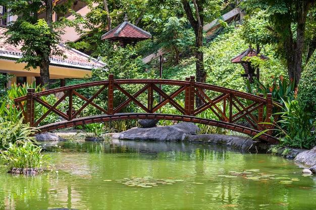 Most łukowy przez ozdobny staw w japońskim ogrodzie tropikalnym w danang, wietnam