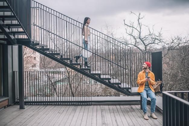 Most miejski. mężczyzna siedzący na schodach, dziewczyna schodząca po moście