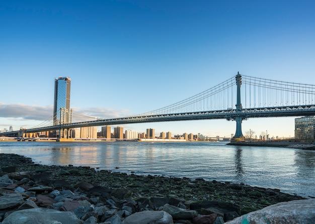 Most na manhattanie z dolnym manhattanie rano z kolorowym światłem nad east river w nowym jorku.