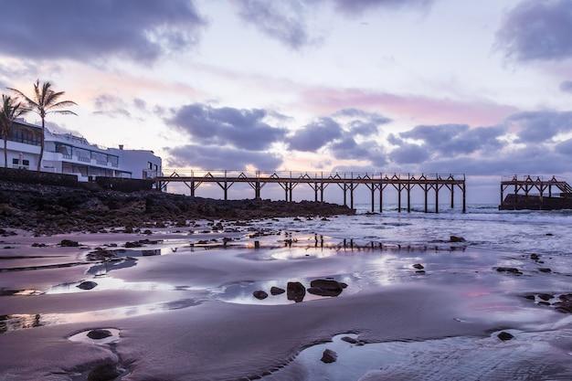 Most na plaży o zachodzie słońca