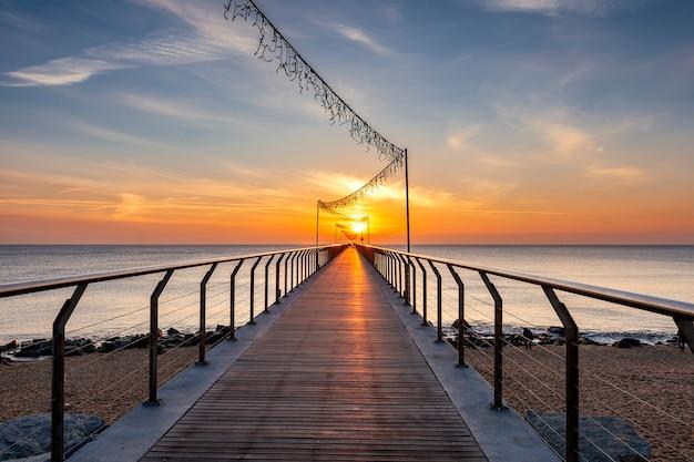 Most na plaży przy wschodem słońca