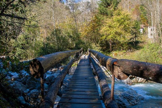 Most nad górskim strumieniem pośrodku gór dolomitów we włoszech
