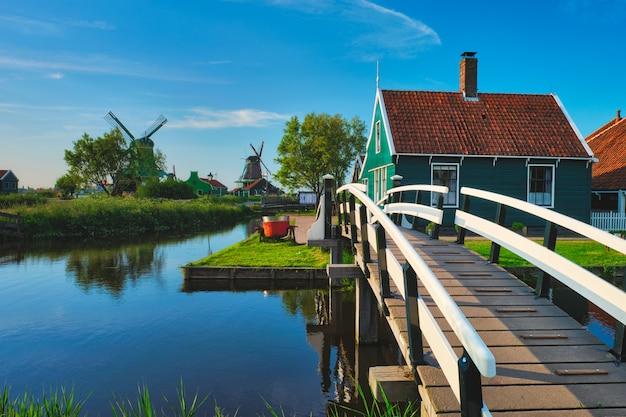 Most nad kanałem przy wiatrakach w zaanse schans w holandii. zaandam, holandia