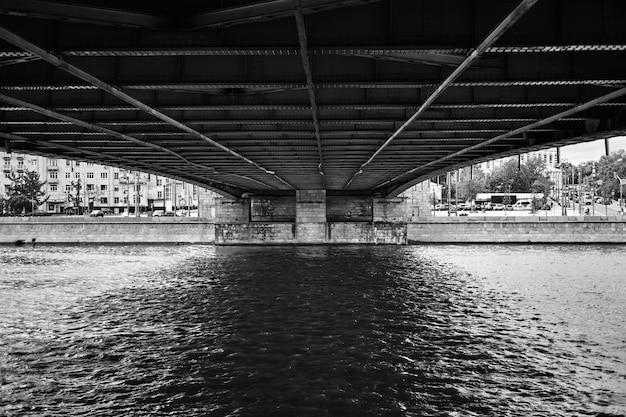 Most nad kanałem z budynkami w tle w czarny i biały
