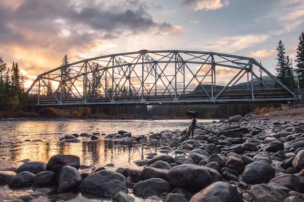 Most nad rzeką dziobową w górach zamkowych z jesiennym lasem rano w parku narodowym banff, kanada