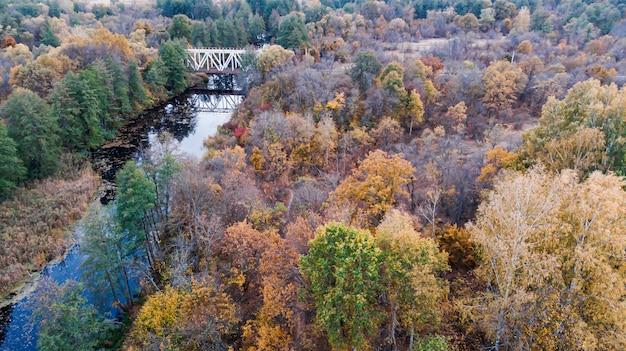 Most nad rzeką między zarezerwowanymi jesiennymi lasami, wzdłuż którego przechodzi kolej.