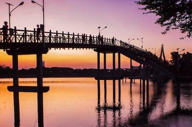 Most o zachodzie słońca. waniliowe niebo w odcieniu rozmycia i różu z tłumem na moście. fotografia sylwetkowa