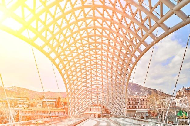 Most pokoju to most dla pieszych nad rzeką kurą w tbilisi, stolicy gruzji. rozbłysk słoneczny