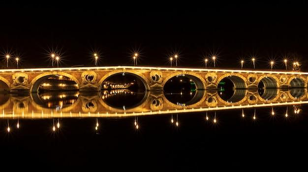 Most pont neuf oświetlony w nocy. piękne odbicie w rzece garonne. tuluza, francja