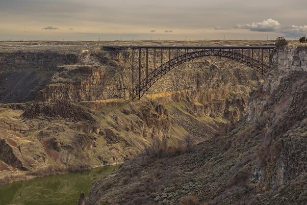 Most pośrodku klifów z zachmurzonym niebem