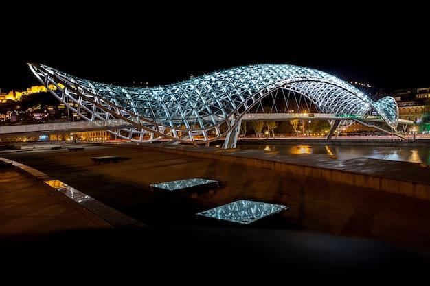 Most pracy w mieście tbilisi, nocne ujęcie mostu dla pieszych, gruzja