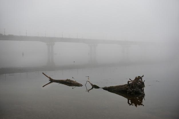 Most przez rzekę dniepr w mglisty poranek z dużą kłodą