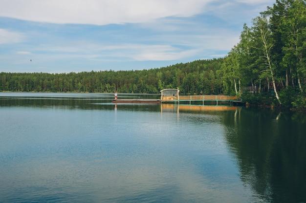 Most rybacki nad rzeką. lądowanie łodzi na jeziorze. woda i transport