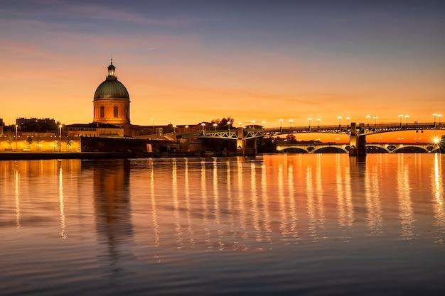 Most saint pierre i kaplica świętego józefa o zachodzie słońca. niesamowite odbicie w rzece garonne. tuluza, francja