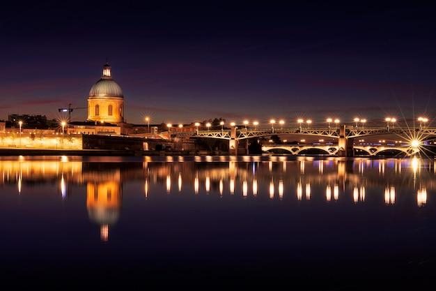Most saint pierre i kaplica świętego józefa w nocy. niesamowite odbicie w rzece garonne. tuluza, francja. europa