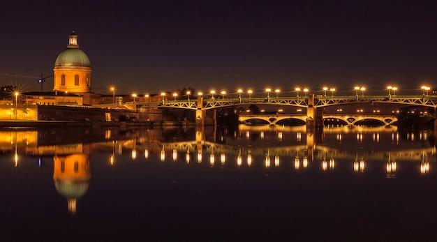 Most saint pierre i kaplica świętego józefa w nocy. niesamowite odbicie w rzece garonne. tuluza, francja