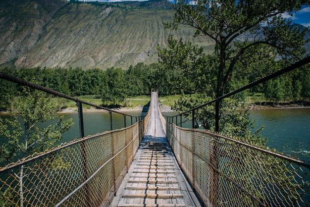 Most wiszący nad rzeką górską. wiszący most otoczony bujną zielenią na tle gór i białych chmur na niebieskim niebie.