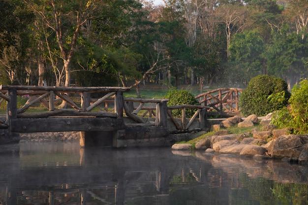 Most ze stawem w parku w czasie wieczoru.