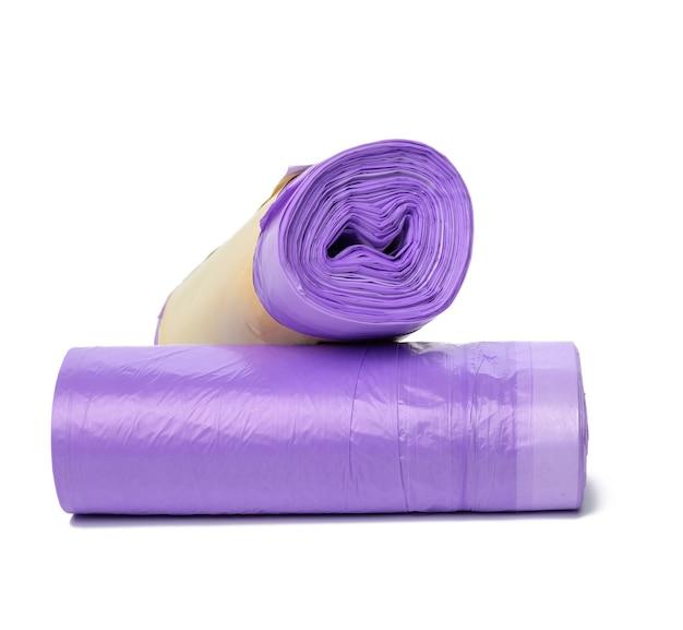 Motek fioletowych plastikowych worków na śmieci ze sznurkami na białym tle
