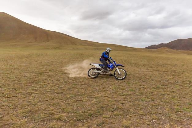 Motocykl podróżnik mężczyzna w kasku na motocyklu po stepach mongolii.