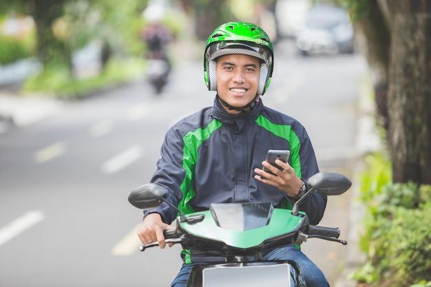 Motocykl taksówkarz przyjmuje zamówienie za pośrednictwem aplikacji internetowej na telefon komórkowy