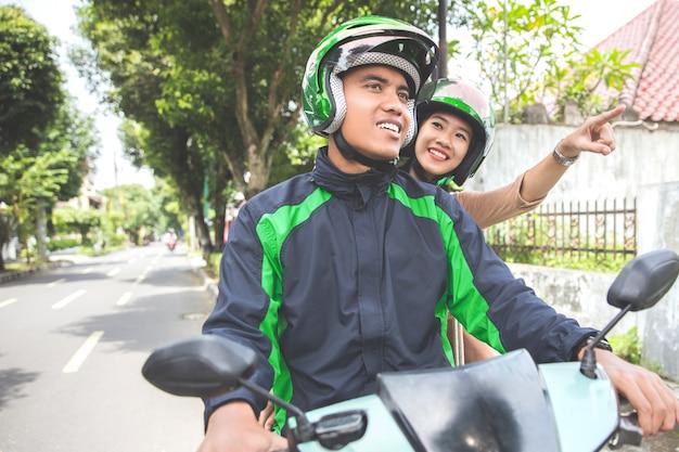 Motocykl taksówkarz zabiera swojego pasażera do miejsca docelowego