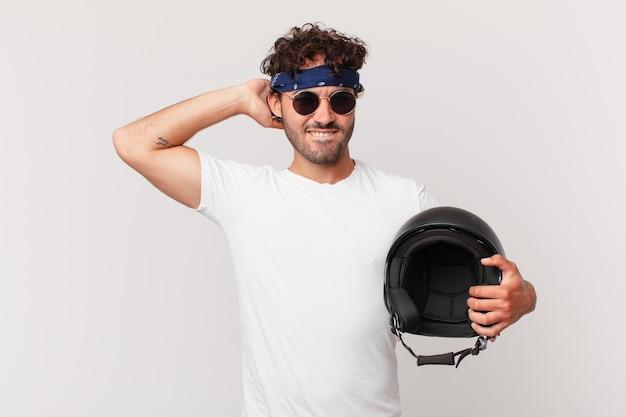 Motocyklista czuje się zestresowany, zmartwiony, niespokojny lub przestraszony, z rękami na głowie, panikuje z powodu błędu